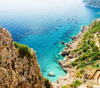 Via Krupp street at Marina Piccola on Capri Island town, Naples, Italy. Landscape with Eoad and Blue Mediterranean Sea at Italian coast. Anacapri in Europe. View on Faraglioni, summer. Amalfi scenery