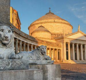 Naples, Italy, view of Basilica Reale Pontificia San Francesco da Paola church on Piazza del Plebiscito, main square of the city, and stone lion sculptures on sunrise