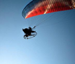 Silhouette di un uomo in parapendio nel cielo che fa il gesto del pollice verso l'alto