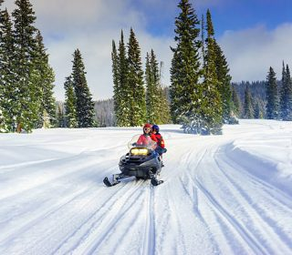 mother and son driving a snowmobile in  colorado, usa