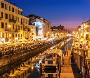 """People dining and promenading along the busy canal """"Naviglio Grande"""" on a Saturday evening."""