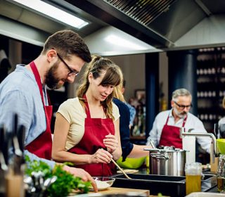 A young chef assisting a cooking class and explaining some tips and tricks